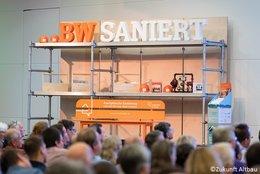 Publikumsaufnahme, die sitzenden Personen sind im unteren Drittel des Bilds von hinten erkennbar. Im Hintergrund ist die Bühne erkennbar. Auf ihr ist im oberen Teil des Bildes ein Baugerüst erkennbar auf dem ein BW-Saniert-Schriftzug in orange und weiß steht.